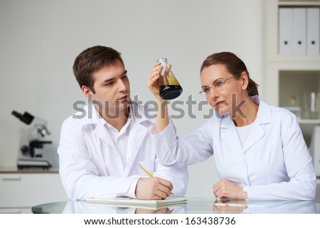 Two scientists looking at glass flask with liquid oil in laboratory - stock photo