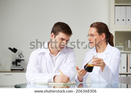 Two scientists looking at glass studying liquid oil in flask in laboratory while analyzing its characteristics - stock photo