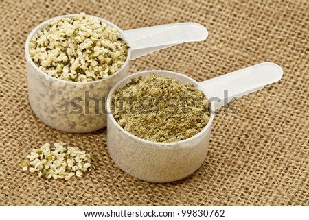 two scoops of raw organic hemp protein powder and shelled hemp seeds - super food rich in nutrients (proteins, antioxidants, amino and fatty acids) - stock photo