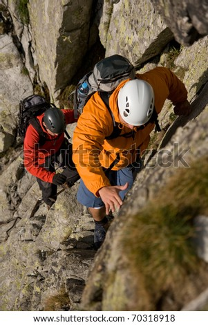 Two scramblers in helmets with backpacks climbing in mountains. Route on the Gerlach in Slovakian High Tatra Mountains. - stock photo