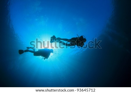 Two Scuba Divers in blue ocean with sunburst - stock photo