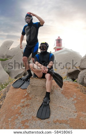 two scuba divers on island with lighthouse and sunset in the background