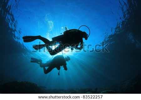 Two Scuba Divers, silhouettes against sunburst, in the ocean beside coral reef - stock photo