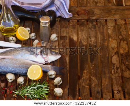 Two Seabass raw fish with shellfish and spices, empty copy space on wooden table   - stock photo