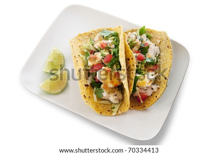 Two seafood tacos on an elegant plate with limes. Isolated on white. - stock photo