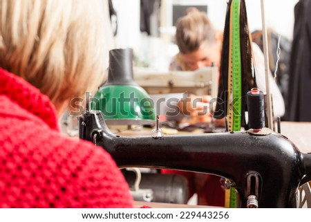 two seamstresses working at the sewing machine in a taylor shop - stock photo