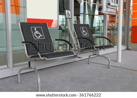 Two seats for people with disabilities in modern airport hall. - stock photo