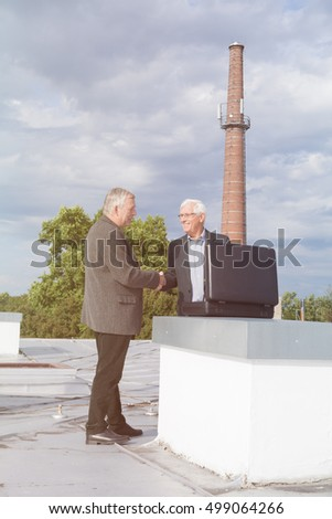 Two senior businessmen with briefcase handshaking and making a business deal outdoors on the roof of a building.
