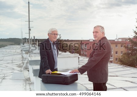 Two senior businessmen with documents making a business deal outdoors on the roof of a building.