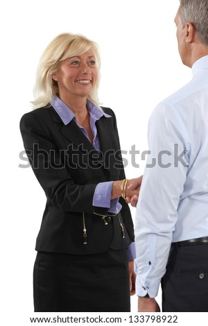 Two senior businesspeople shaking hands - stock photo