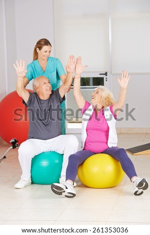 Two senior citizens doing sports in physiotherapy during rehab - stock photo