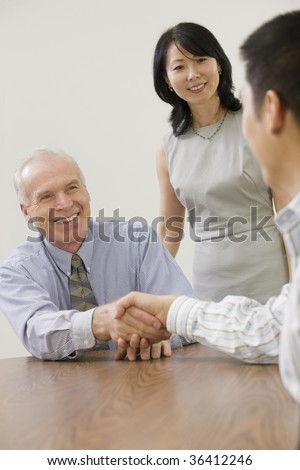 Two senior executives congratulating junior team member. - stock photo