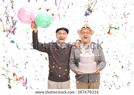 Two senior gentlemen celebrating birthday with a cake and balloons isolated on white background - stock photo