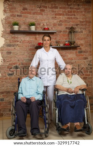 Two Senior In Wheelchairs With Nurse, Looking At Camera - stock photo