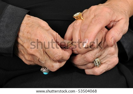 Two senior lady holding each others hands.