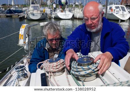 Two senior men preparing a sailing boat in the harbor of Nieuwpoort. - stock photo