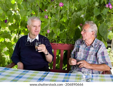 Two senior men sitting on terrace and drinking water - stock photo