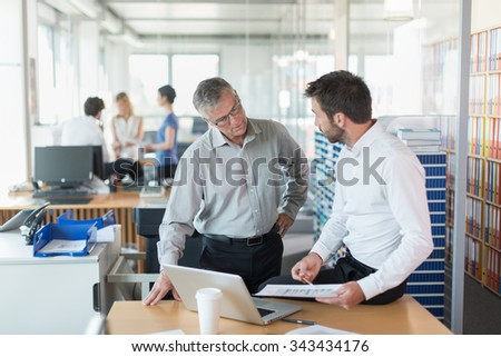 Two senior partners standing in front of a desk in a luminous open space with glass walls. They are analyzing balance sheets on a laptop. They are wearing a shirt and suit pants.