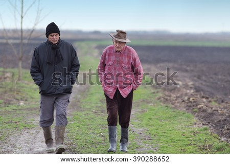 Two senior peasants walking on the field in winter time - stock photo