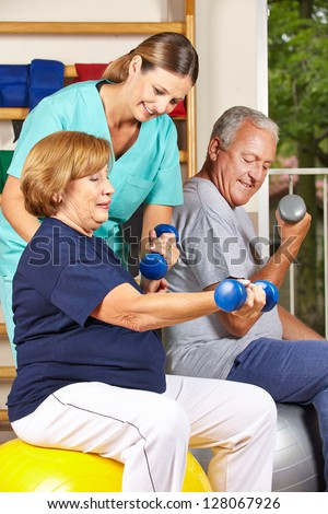 Two senior people doing dumbbell fitness training with physiotherapist - stock photo