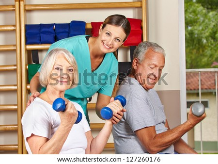 Two senior people in gym doing fitness exercises with dumbbells - stock photo