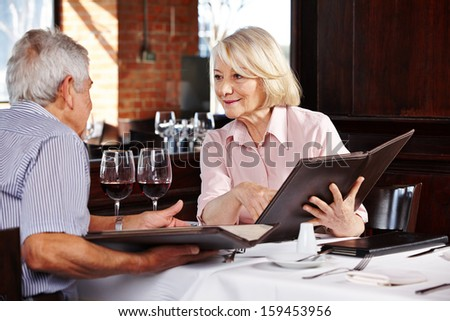 Two senior people with menu in restaurant for lunch - stock photo