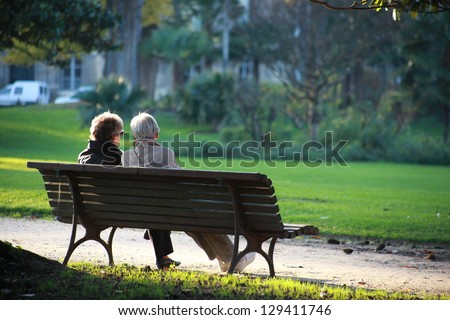 Two senior sat on a bench - stock photo