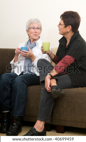 Two senior women drinking coffee, chatting and having a good time together as girl-friends. - stock photo