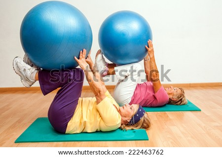 Two Senior women exercising muscles with Swiss balls in health club.