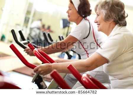 Two senior women exercising on training machines - stock photo