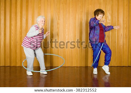 Two senior women exercising with hula hoops