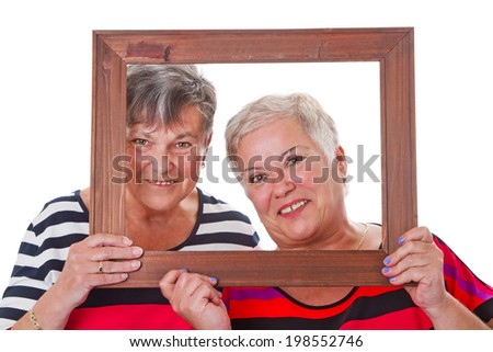 Two senior women looking through a picture frame - stock photo