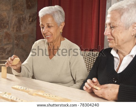 Two senior women playing dominoes enjoying retirement - stock photo