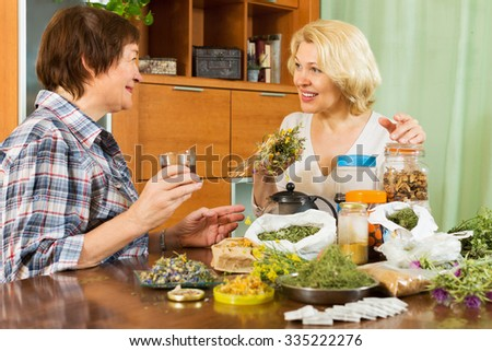 Two senior women sitting at the table with herbal tea and herbs