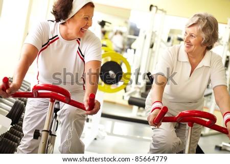 Two senior women training on simulator and smiling - stock photo