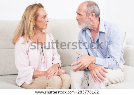 Two seniors talking while sitting on a coach