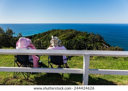 two seniors watching for humpback whales passing the coast at byron bay lighthouse - stock photo
