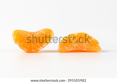 two separated segments of tangerine on white background