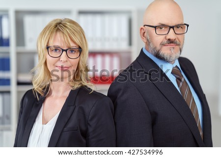 Two serious business people in suit jackets and eye glasses stand near shelf and shoulder to shoulder - stock photo