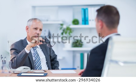 Two serious businessmen speaking and working at the office - stock photo