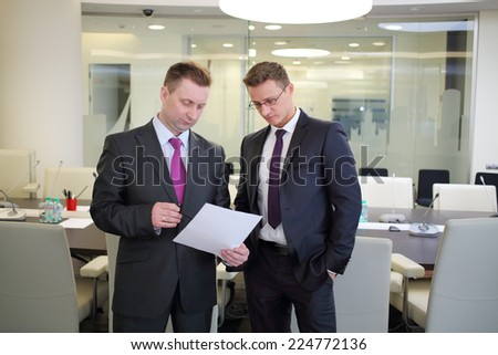 Two serious businessmen standing with a blank sheet of paper in conference hall - stock photo