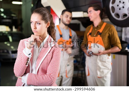 Two serious mechanics trying to cheat unhappy client at workshop - stock photo