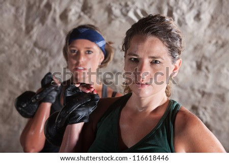 Two serious sweating women holding weights indoors - stock photo