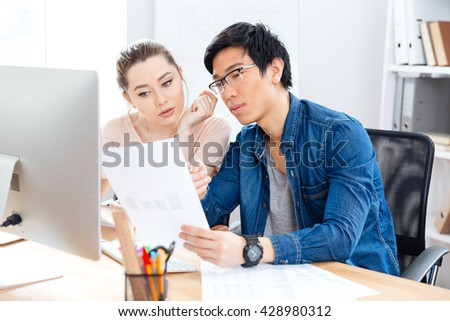 Two serious young businesspeople working with documents in office together - stock photo