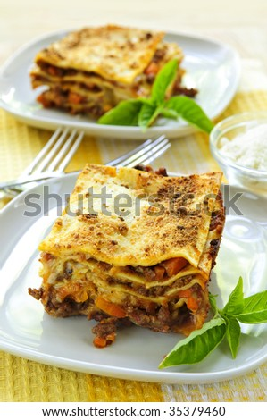 Two servings of fresh baked lasagna on plates - stock photo