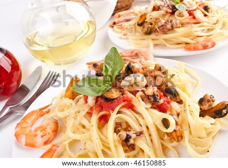 two servings of pasta with marinara sauce and seafood - stock photo