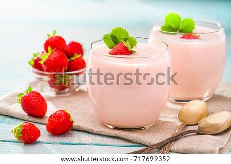 two servings of  pink yogurt with fresh strawberries on a turquoise wooden background