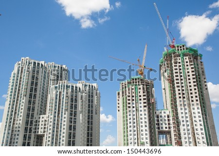 two sets of building finished and unfinished against blue sky at the construction site - stock photo