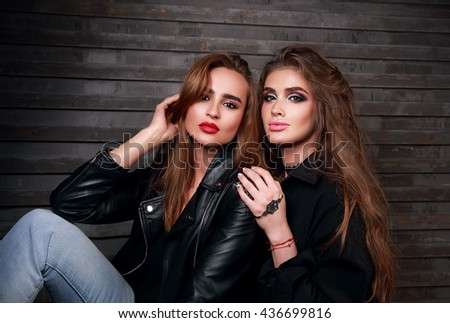Two sexy beautiful woman with bright makeup, long hairstyle and in black jackets on wall background