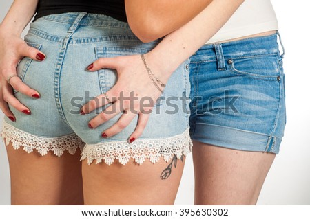 Two sexy female buttocks. Sexy woman body in jeans shorts.  The model is back. Great ass.  - stock photo